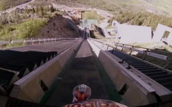 Il saute en moto cross depuis une rampe de saut à ski