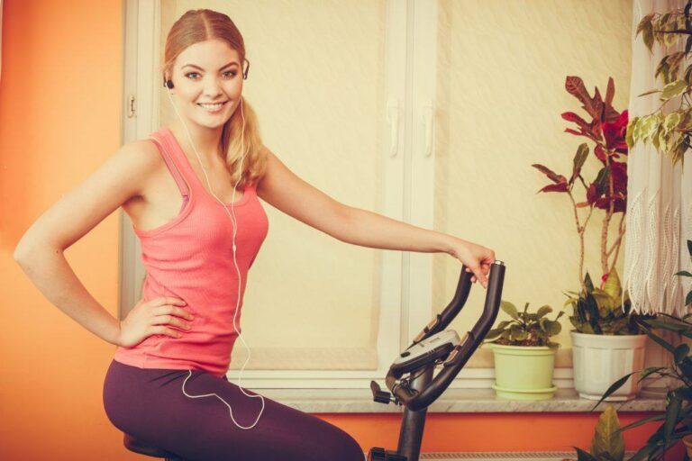 une femme fait du vélo d'appartement à la maison