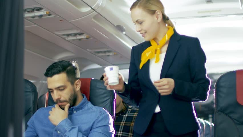 Une hôtesse de l'air donne un café au passager d'un avion