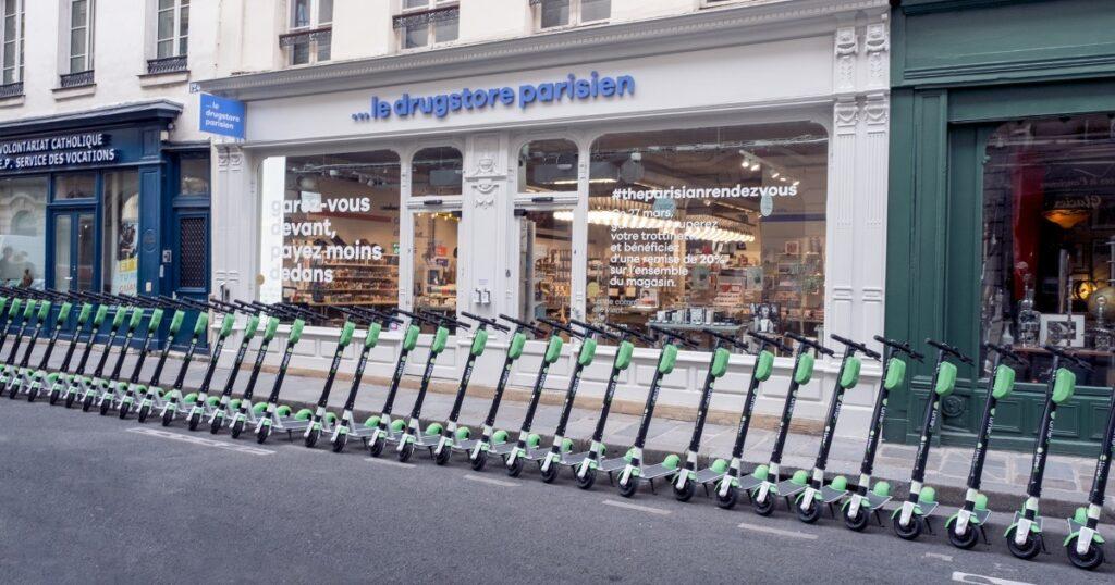 The Parisian Rendez-Vous : des trottinettes électriques libre service garées devant le drugstore parisien