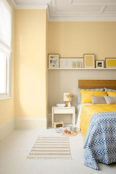 Mur de couleur jaune pâle. Tendance en 2019. Une étagère avec une accumulation de cadres.