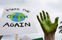 "pancarte ""make earth green again"" avec une main verte en premier plan."