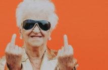 Silver influenceuse : grand mère en lunettes de soleil aviateur qui fait des doigts d'honneur devant un fond orange.