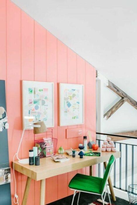 Bureau face à un mur couleur corail avec deux cadres accrochés.