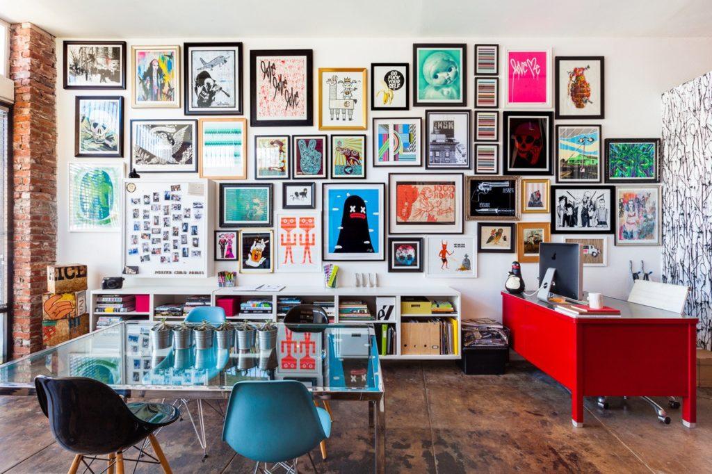 Mur de cadres colorés. Affiches illustrées. Bureau rouge vif.