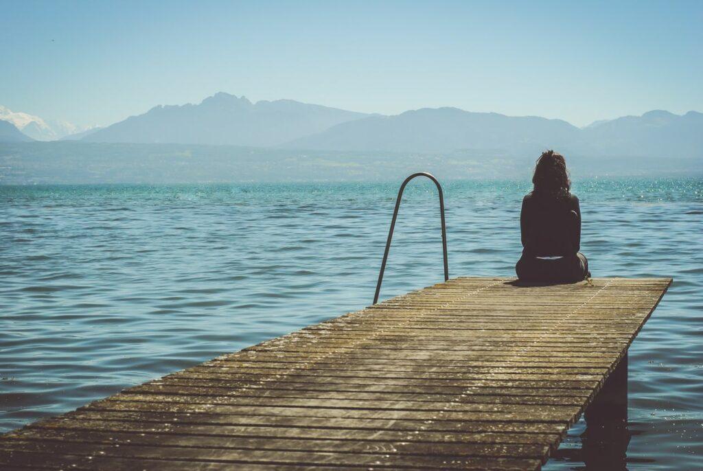 Femme assise de dos au bout d'un ponton avec les pieds dans l'eau d'un lac. Montagnes en arrière plan.
