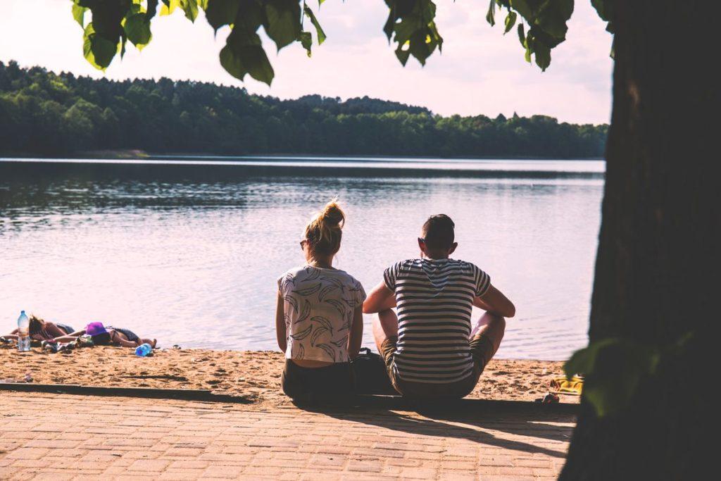 Couple de dos, assis devant un plan d'eau.