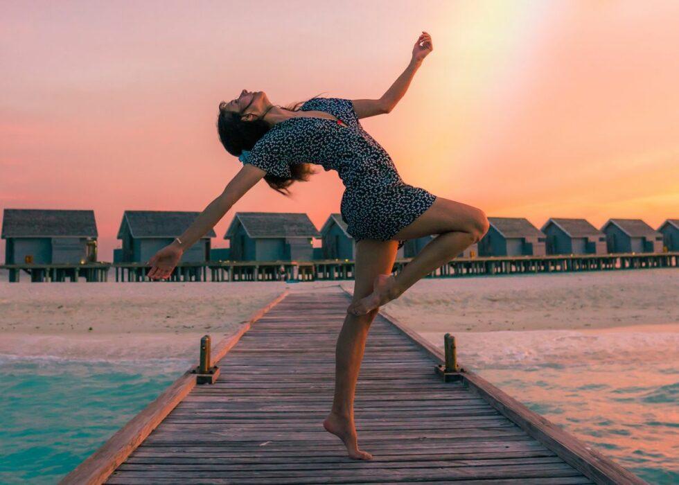 Femme qui danse sur un ponton pendant un coucher de soleil avec un arc-en-ciel derrière elle.