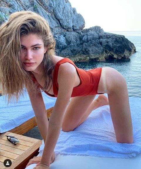 Portrait de Victoria Sampaio en maillot de bain posant à quatre pattes devant la mer.