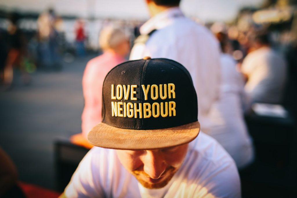 """Homme portant une casquette avec le texte """"love your neighbour"""" brodé dessus."""