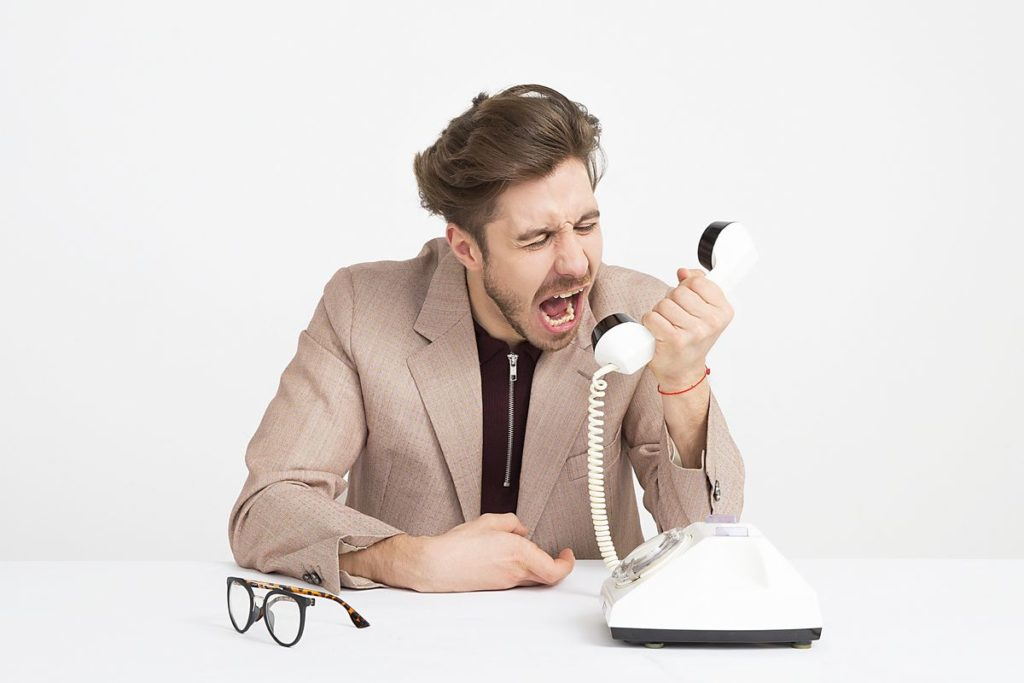 Homme en costume beige qui crie dans un téléphone.