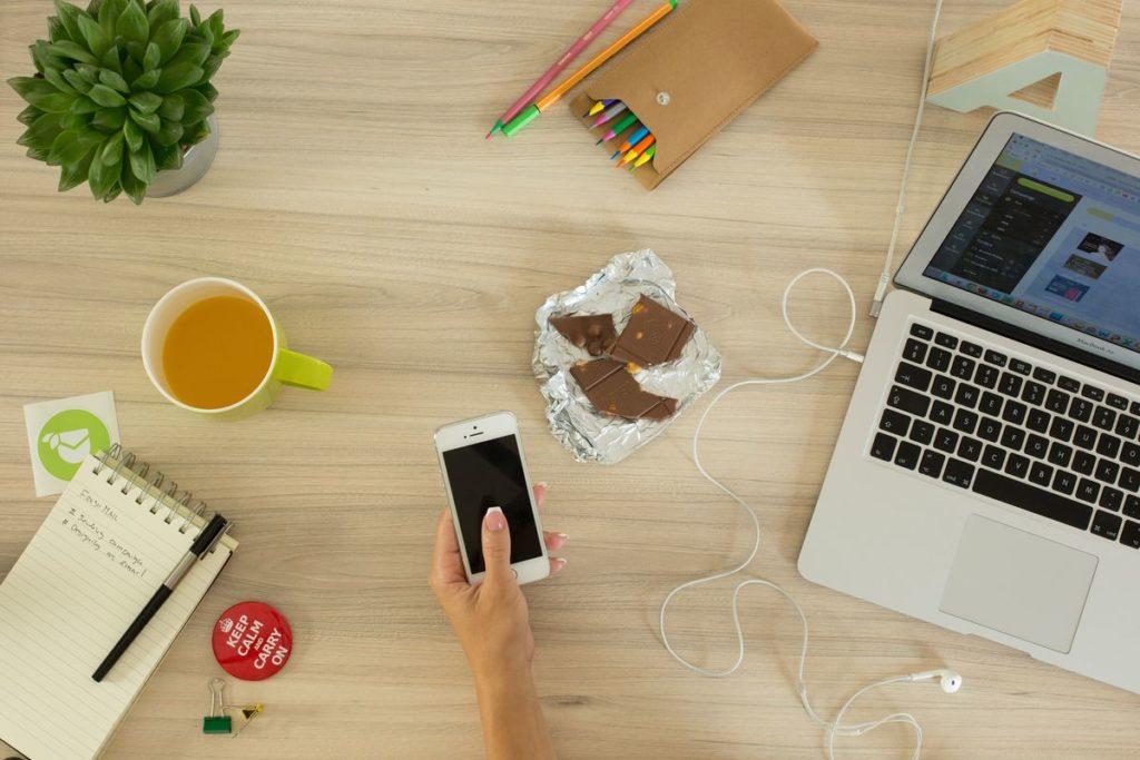 Flatlay d'un bureau avec un bloc note, des crayons de couleur, du chocolat, un ordinateur portable et une tasse de thé.