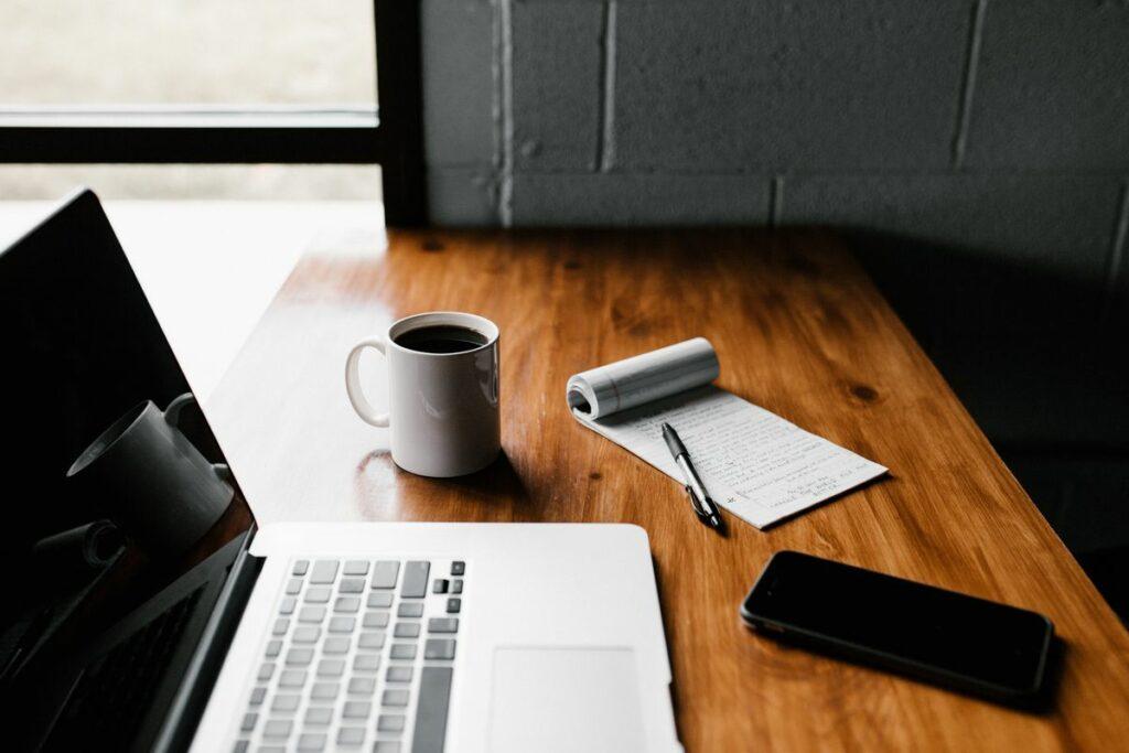 Ordinateur portable posé sur un bureau en bois avec un bloc note, une tasse de café et un smartphone.