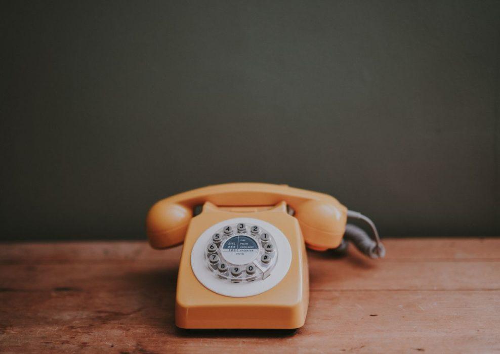 Téléphone orange sur une table en bois devant un mur kaki.