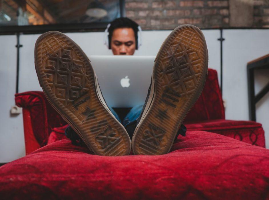 Homme travaillant sur son ordinateur sur la méridienne d'un canapé.