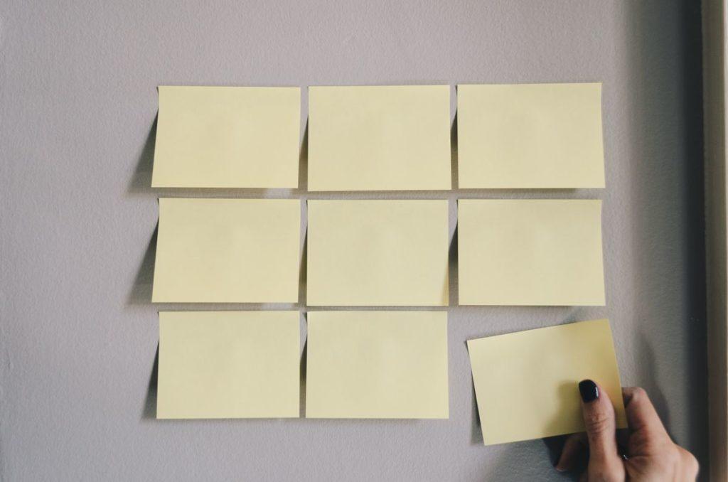 Neuf postit jaunes pale sur un mur gris.