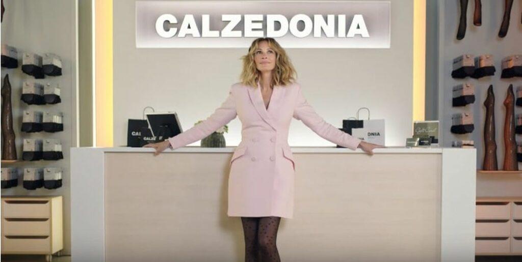 Julia Roberts adossée au comptoir d'une boutique Caledonia en tailleur rose et collants noirs.