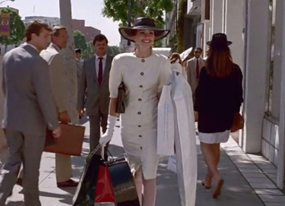 Julia Roberts en tailleur blanc et chapeau noir avec les bras chargés de shopping dans le film Pretty Woman.