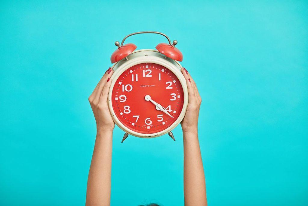 Réveil matin orange tenu à bout de bras par une femme devant un fond bleu turquoise.