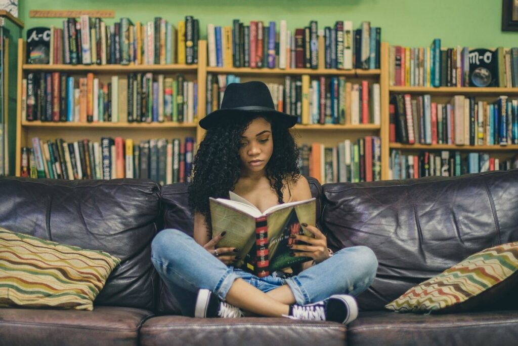 Ado lisant sur un canapé devant une bibliothèque.