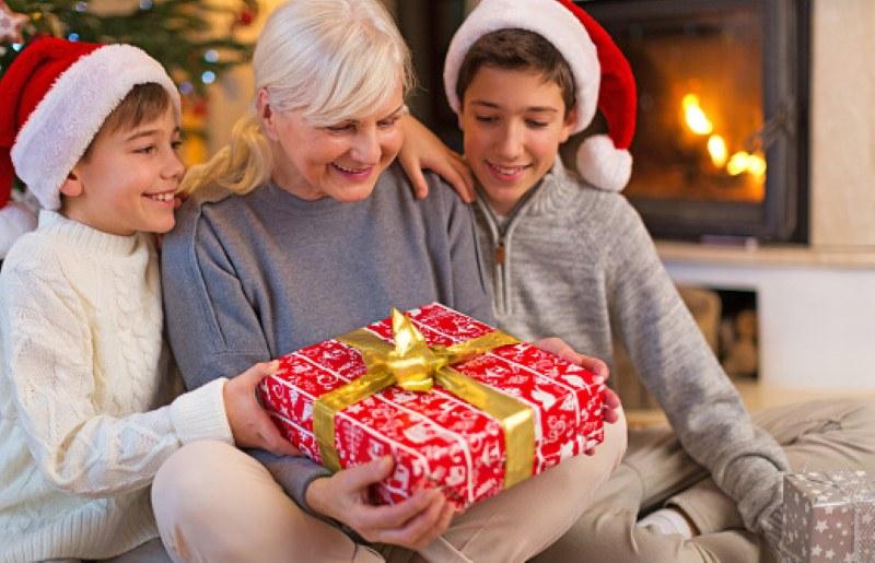 Une grand-mère ouvre son cadeau de Noël avec ses petits enfants