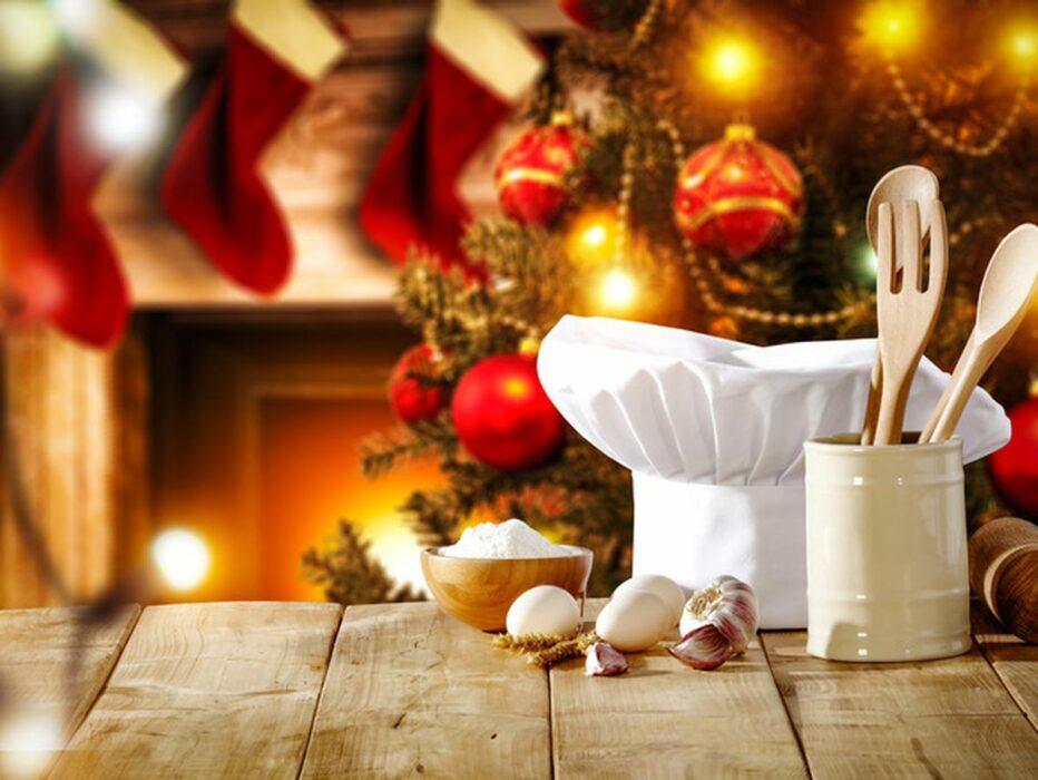 Ambiance de Noël. Couvert en bois et ingrédients pour cuisiner au premier plan. Chaussettes suspendues à la cheminée à l'arrière plan