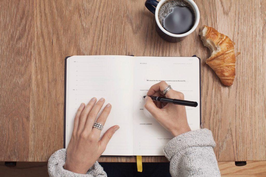 Femme écrivant dans un carnet vue de dessus avec café et croissant.