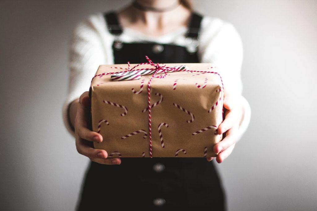 cadeau tendu par une femme en salopette