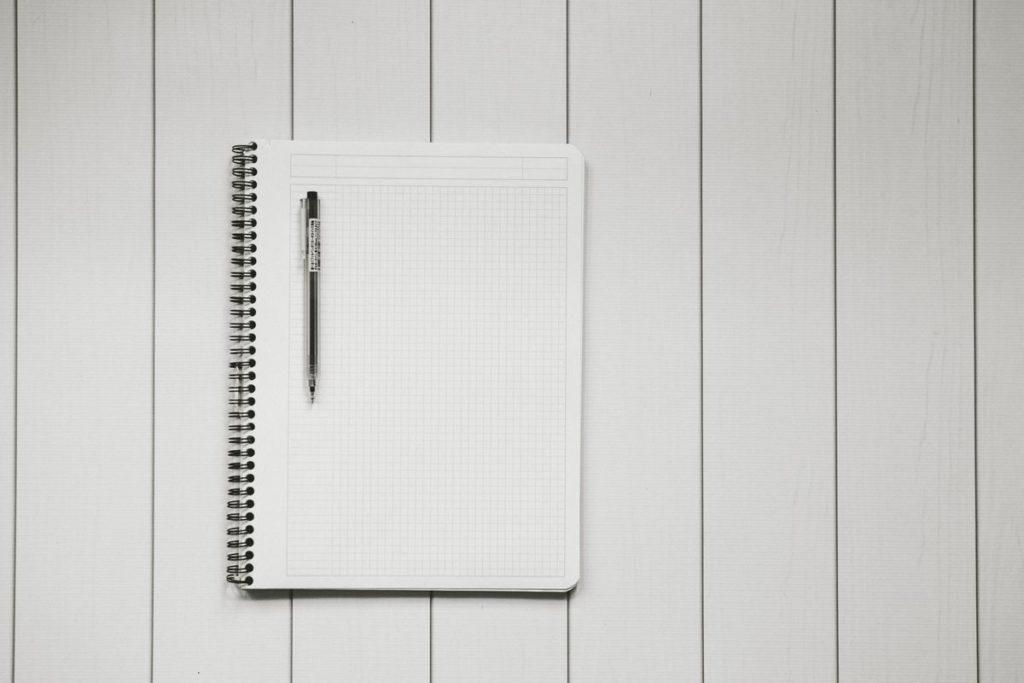 Carnet vierge et stylo sur fond blanc.