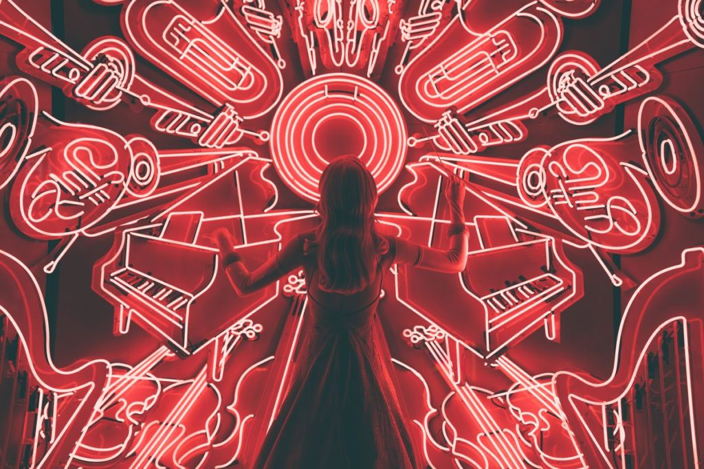 Femme regardant un mur de néons en formes d'instruments de musique