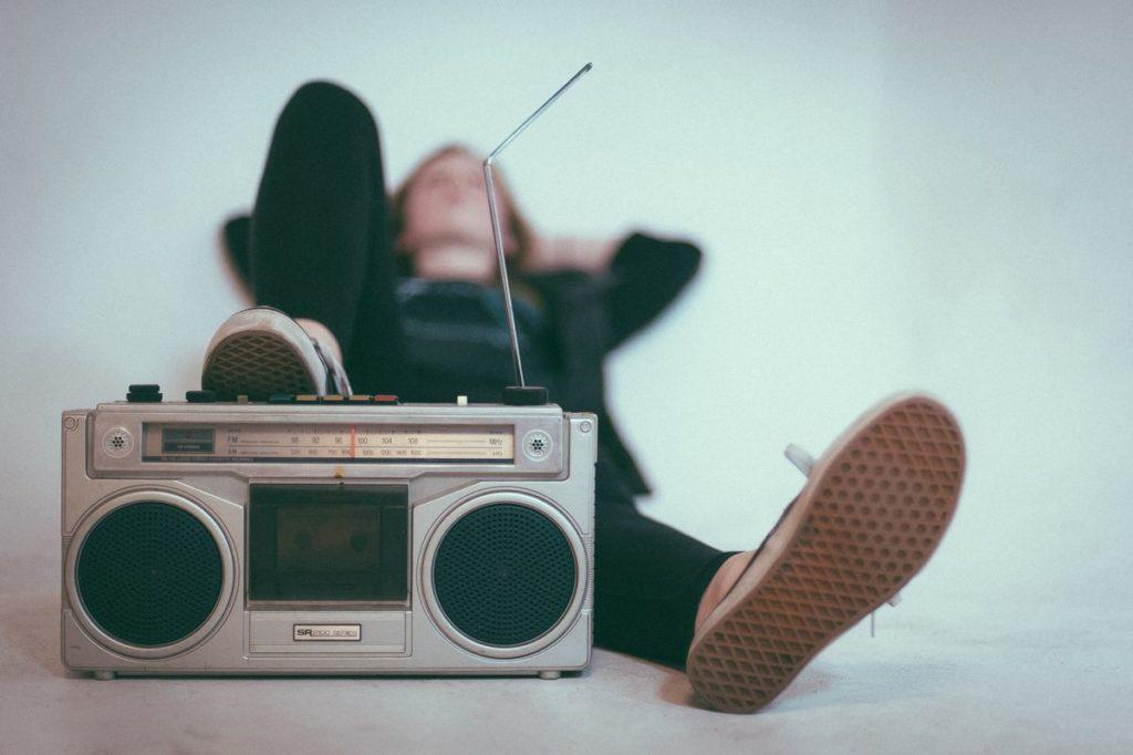 Personne sur le dos avec les pieds posés sur un poste de radio