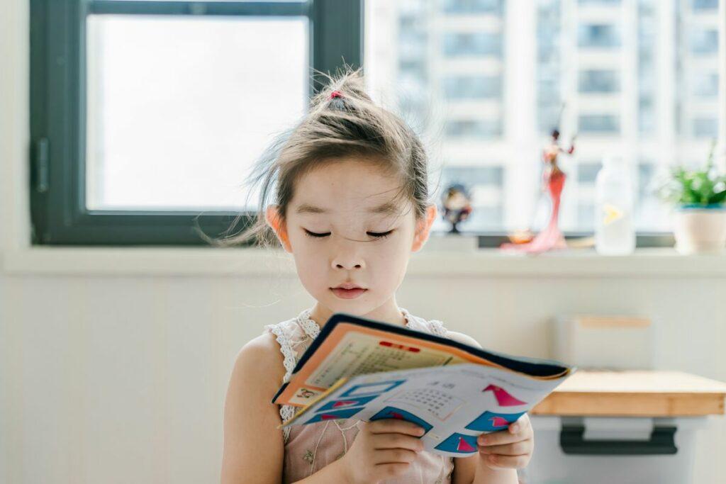 Fillette lisant une revue pour enfant.