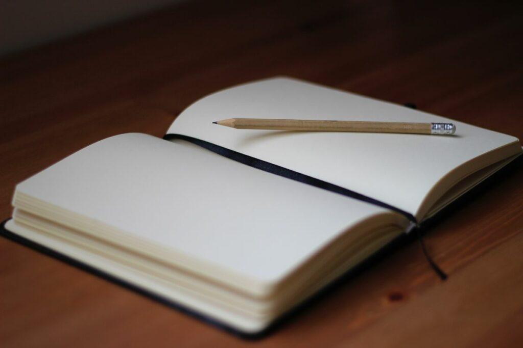 Carnet posé ouvert sur une table en bois avec un crayon à papier posé dessus.