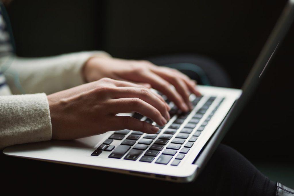 Mains qui tapent sur le clavier d'un ordinateur portable.