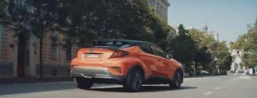 voiture toyota hybride orange qui roule en ville.