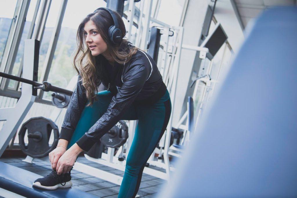Femme à la salle de sport avec un casque audio sur les oreilles.